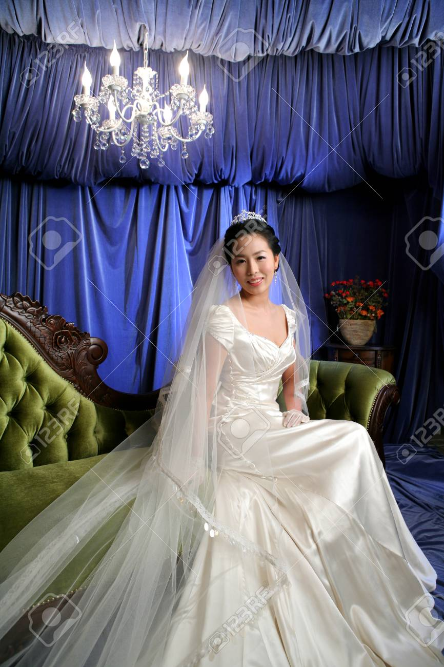 Asian bride in wedding dresses posing in a studio as sitting