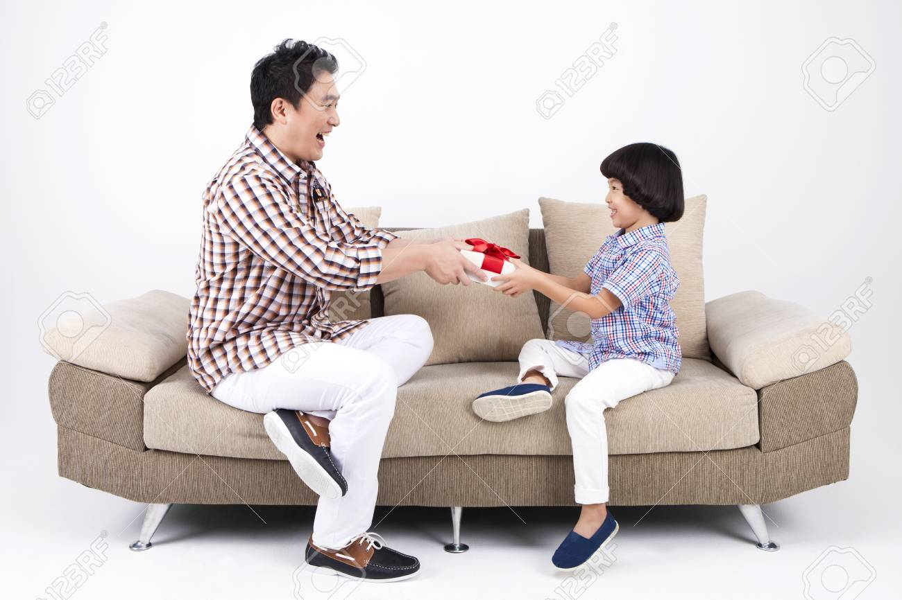 Fabulous Asian Dad Giving T To Son On Sofa Bed Isolated On White Gmtry Best Dining Table And Chair Ideas Images Gmtryco