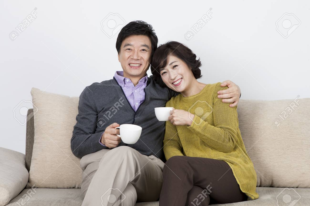 Brilliant Asian Middle Aged Couple Drinking Coffee On Sofa Bed Isolated Gmtry Best Dining Table And Chair Ideas Images Gmtryco