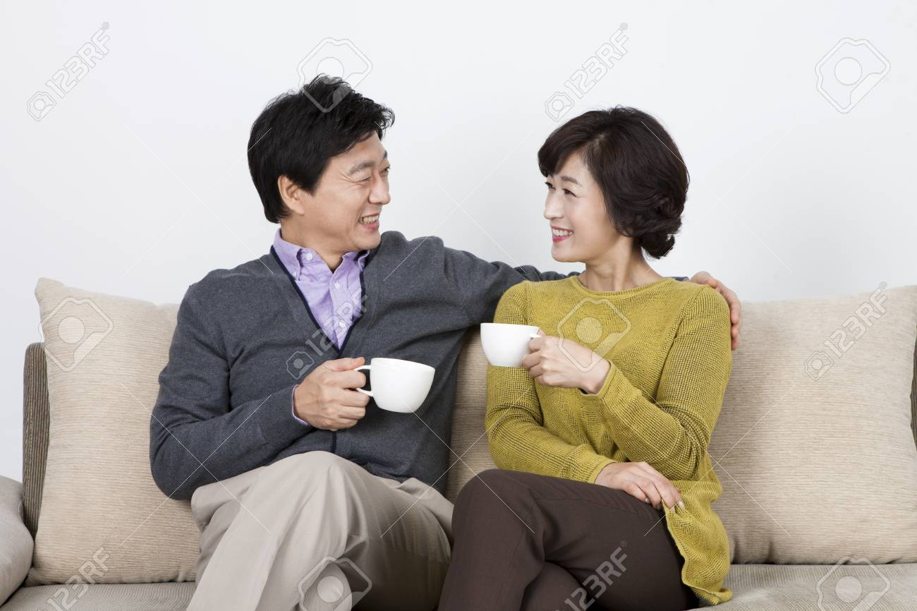 Astounding Asian Middle Aged Couple Drinking Coffee On Sofa Bed Isolated Gmtry Best Dining Table And Chair Ideas Images Gmtryco