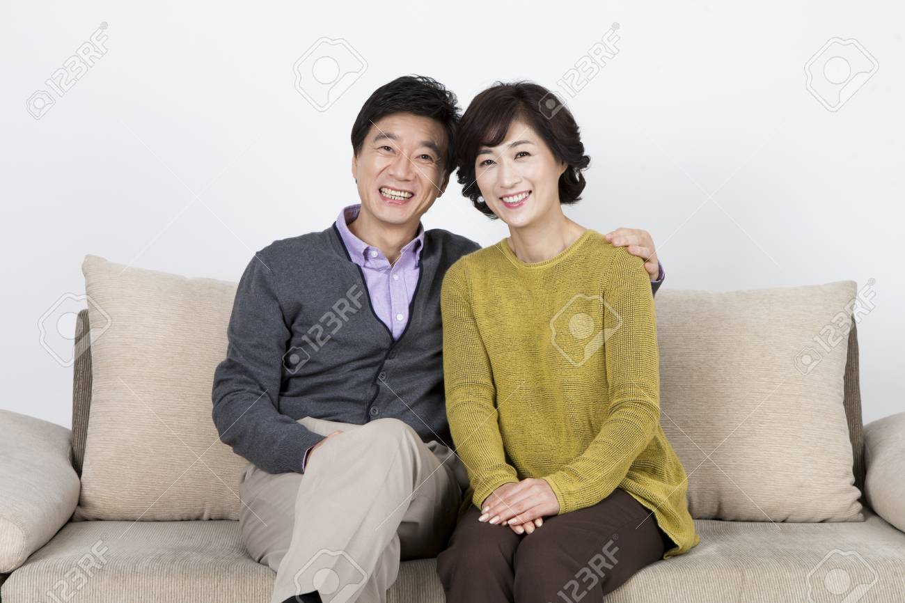 Groovy Asian Middle Aged Couple Having Good Time On Sofa Bed Isolated Gmtry Best Dining Table And Chair Ideas Images Gmtryco