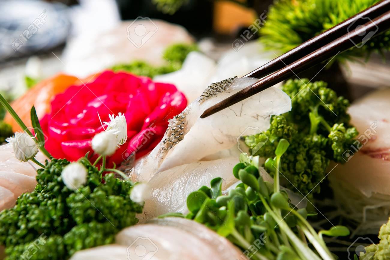 fish sashimi on chopsticks - 120073421
