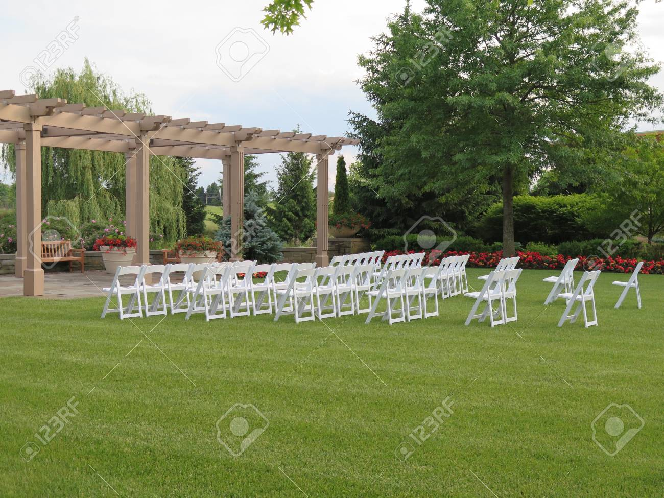 White empty chairs set for outdoor wedding ceremony