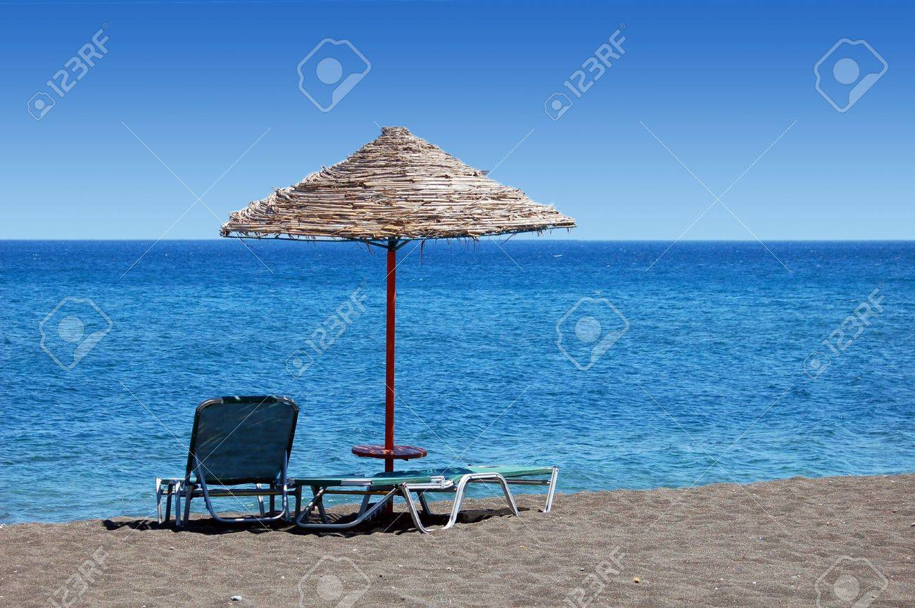 An Umbrella And Sun Bathing Chairs On The Black Beach Of Perissa ...