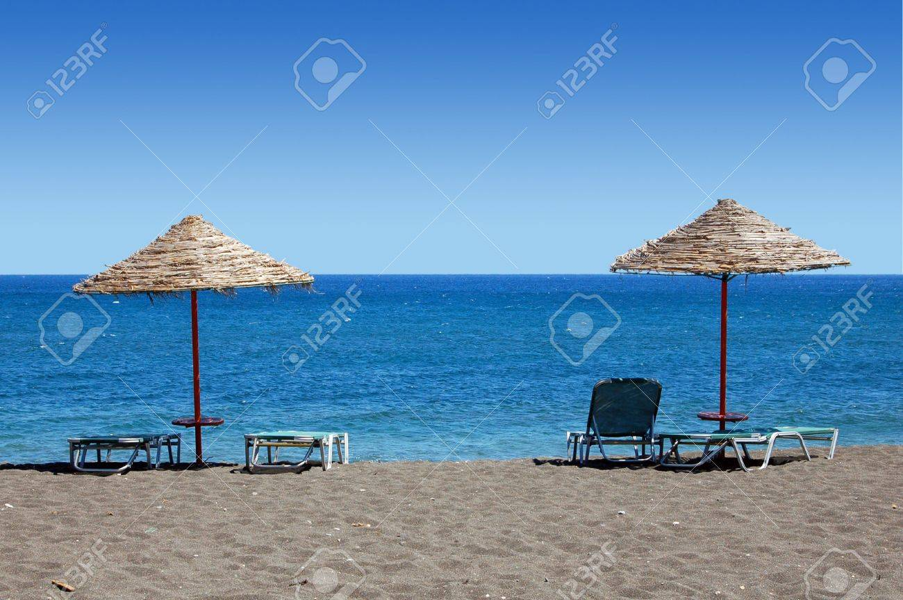 Umbrellas And Sun Bathing Chairs On The Black Beach Of Perissa ...