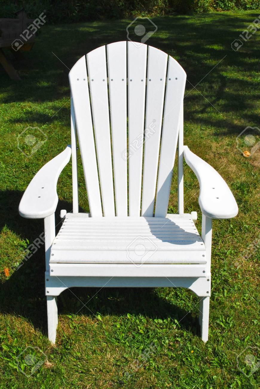 ein weißer adirondack-stuhl in einer grasartigen land-einstellung