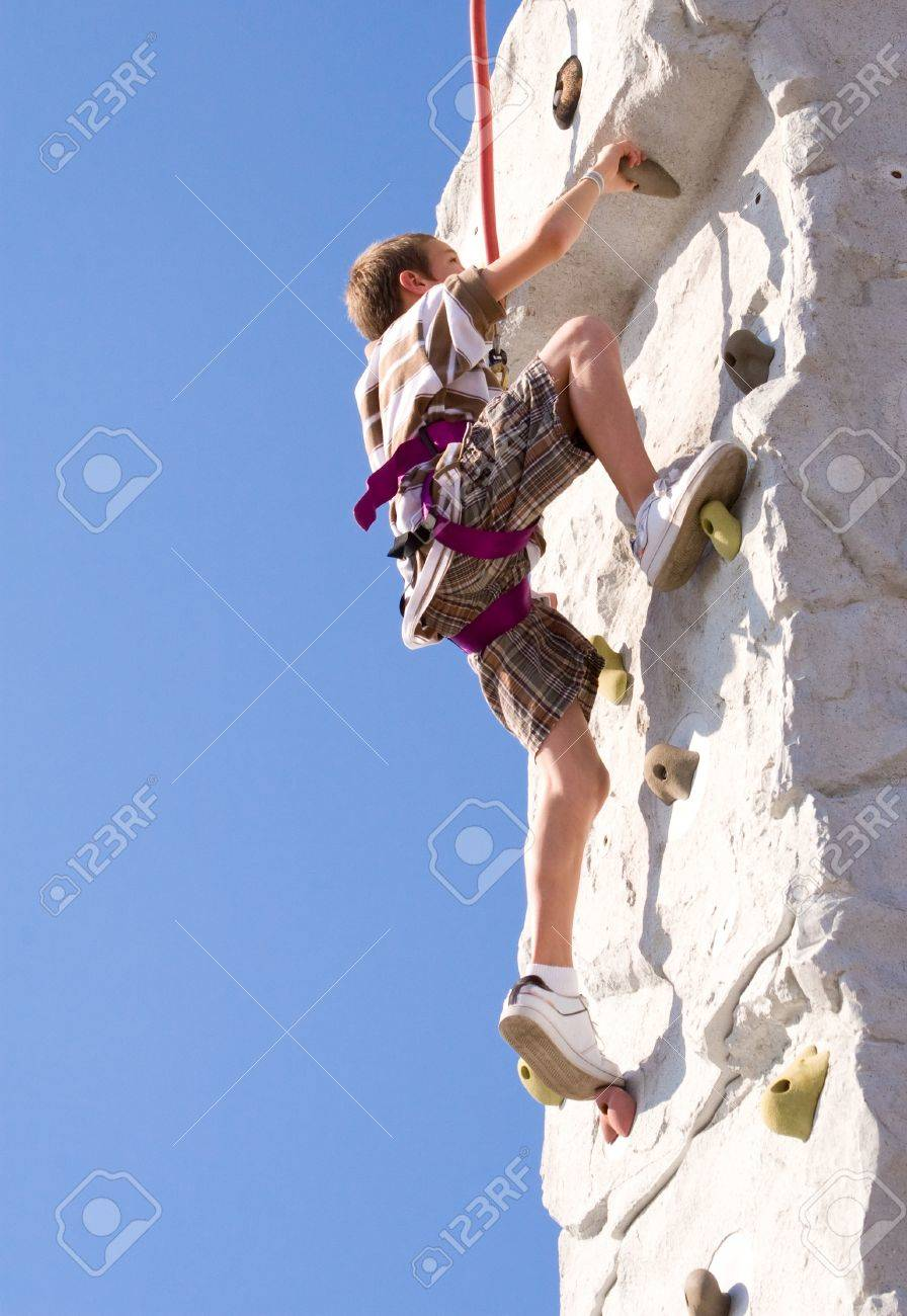 Young boy climbing up an artificial rock wall Stock Photo - 10893904