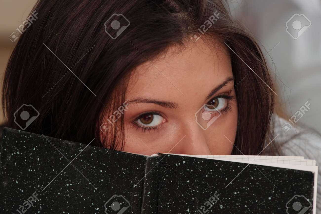 Young beautieful, natural looking, caucasian, brunette girl learning on the flor with red pen and books Stock Photo - 4679800