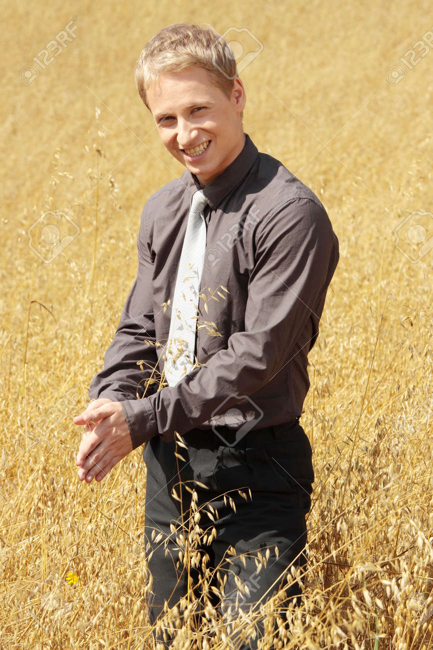 Young modern farmer in suit standing in field of oats Stock Photo - 5401239