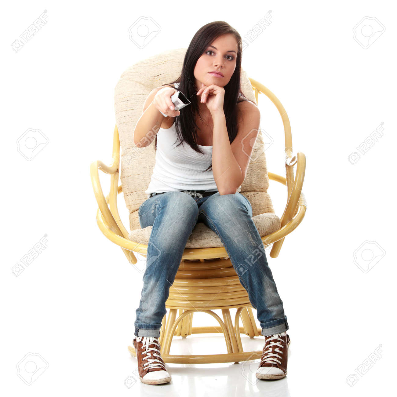 Young woman watching TV with remote control in hand while sitting on armchair isolated - view from TV - Change the channel concept Stock Photo - 5930020