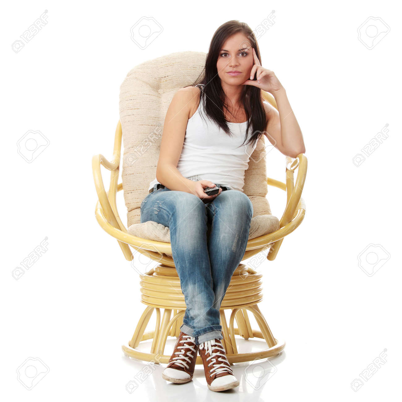 Young woman watching TV with remote control in hand while sitting on armchair isolated - view from TV - Change the channel concept Stock Photo - 5930233