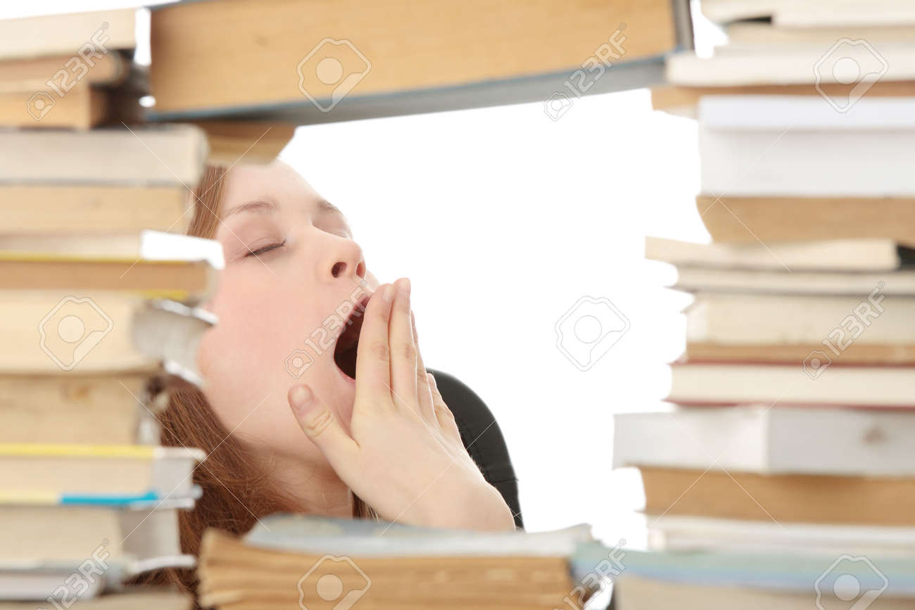 Young woman sitting behind books - tired Stock Photo - 6376419