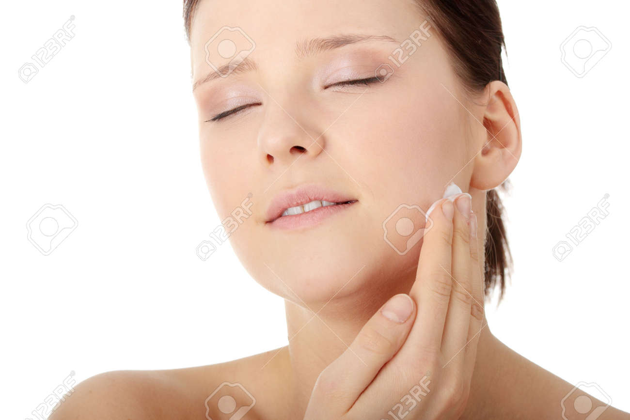 Woman applying moisturizer cream on face. Close-up fresh woman face. Stock Photo - 6599330