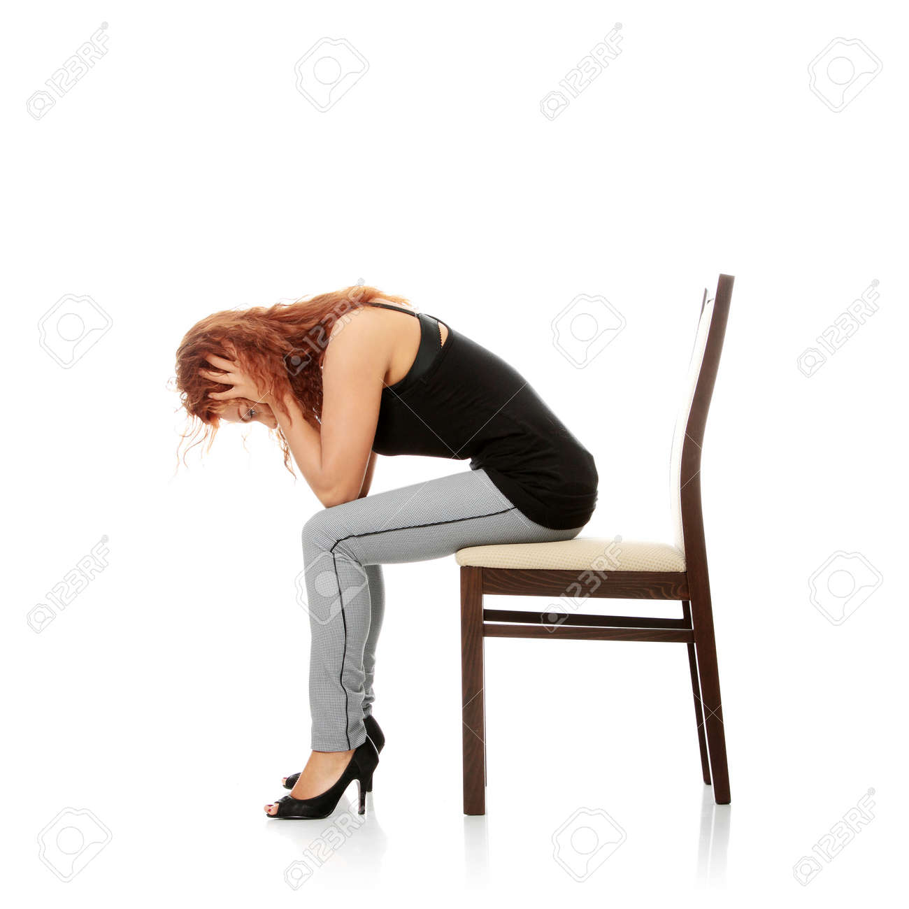 A worried and afraid young woman sitting on chair. Isolated Stock Photo - 8827383