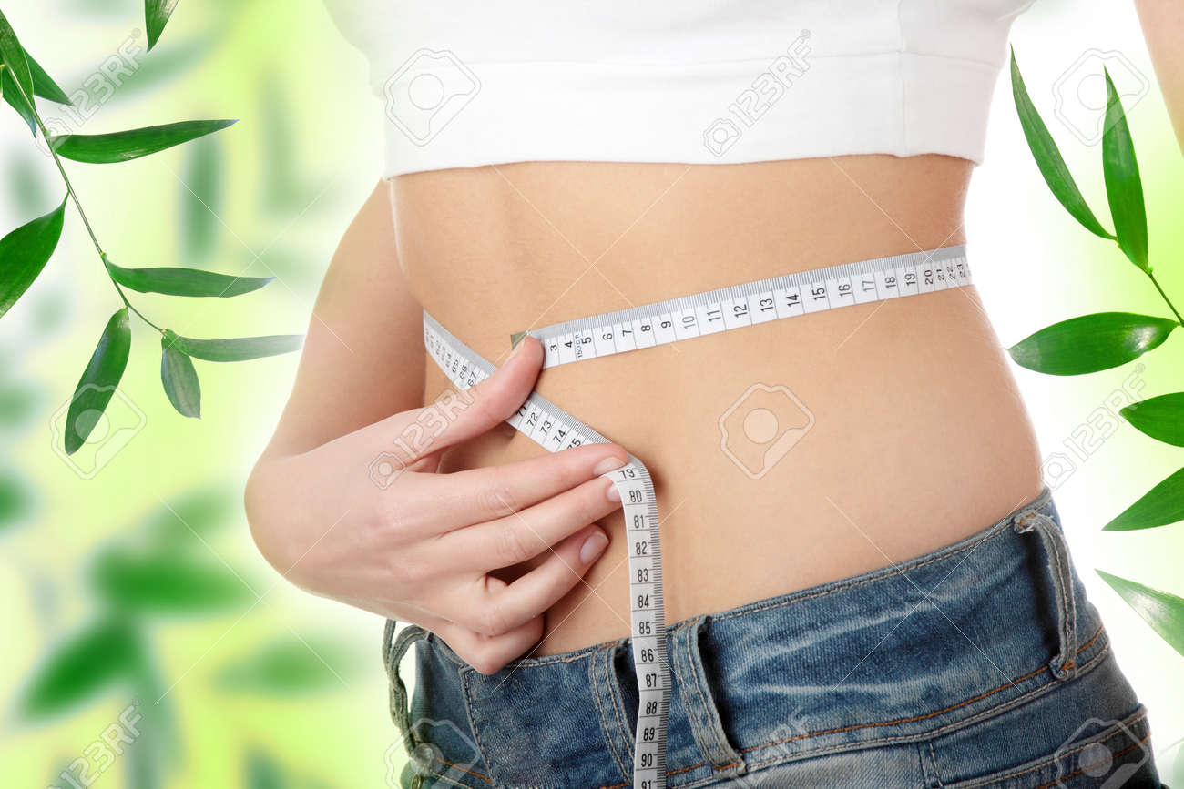 Sexy, fit, young woman measuring her waist Stock Photo - 9030436