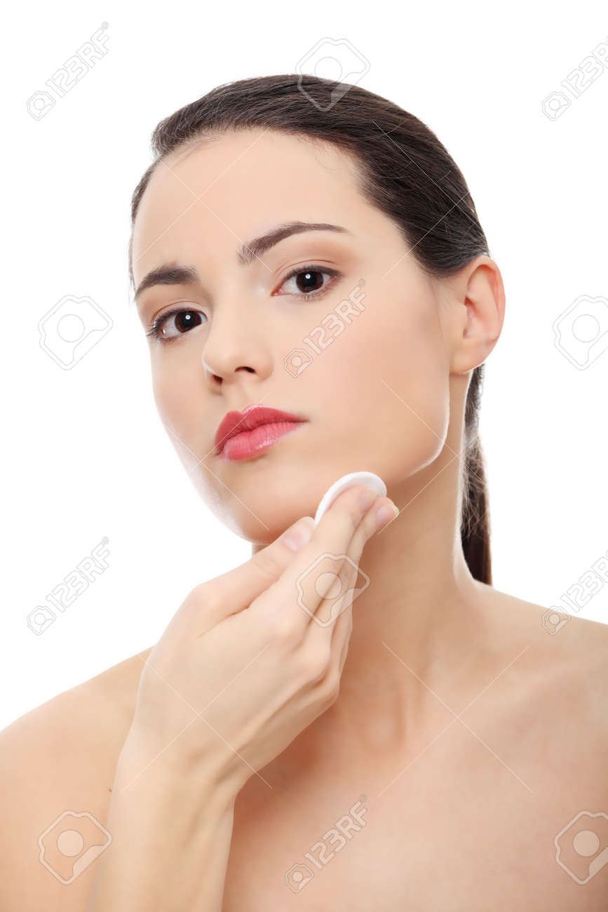 Young beautiful caucasian woman using a cotton pad to remove her make-up. Isolated on white Stock Photo - 9033371
