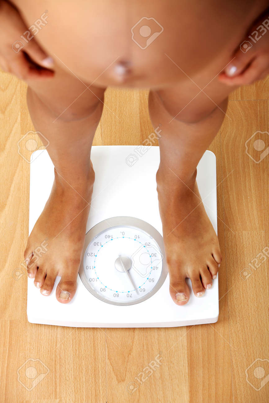 Pregnant woman checking her weight on scale Stock Photo - 10601725