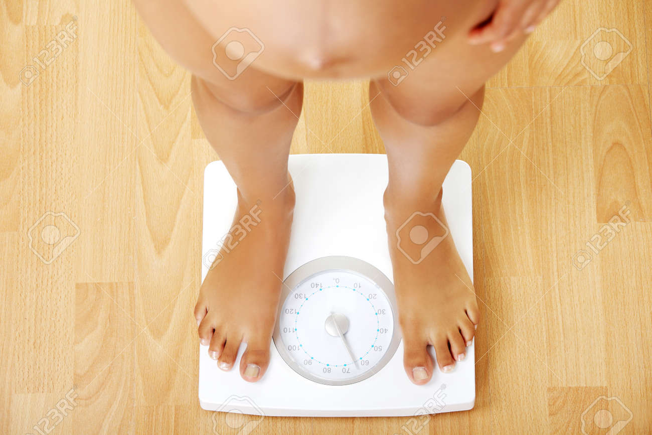 Pregnant woman standing on the scales - view from the top on the scales. Stock Photo - 12112350