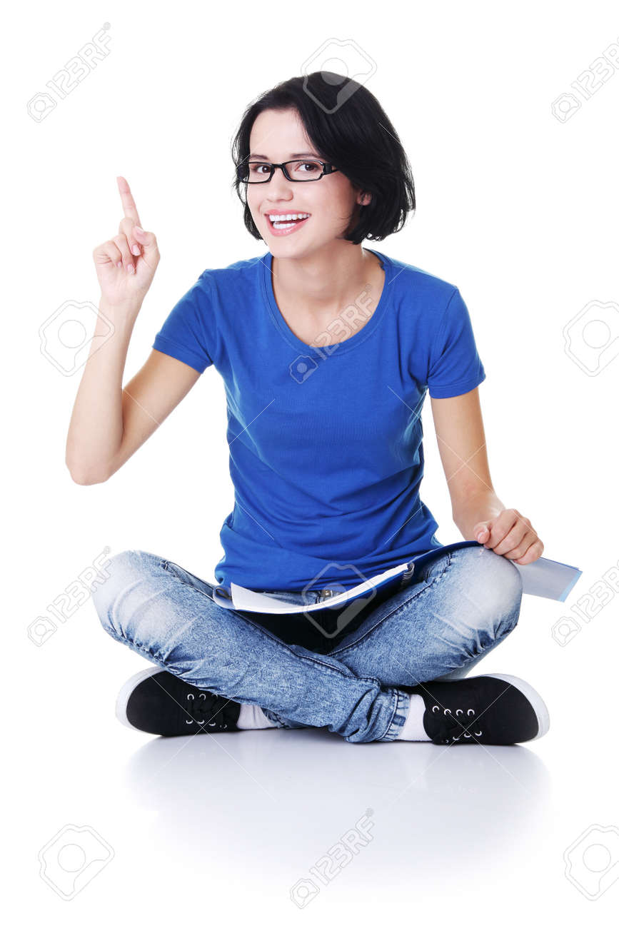 Studying happy young woman reading her notebook for school and pointing on copy space. Stock Photo - 15010940