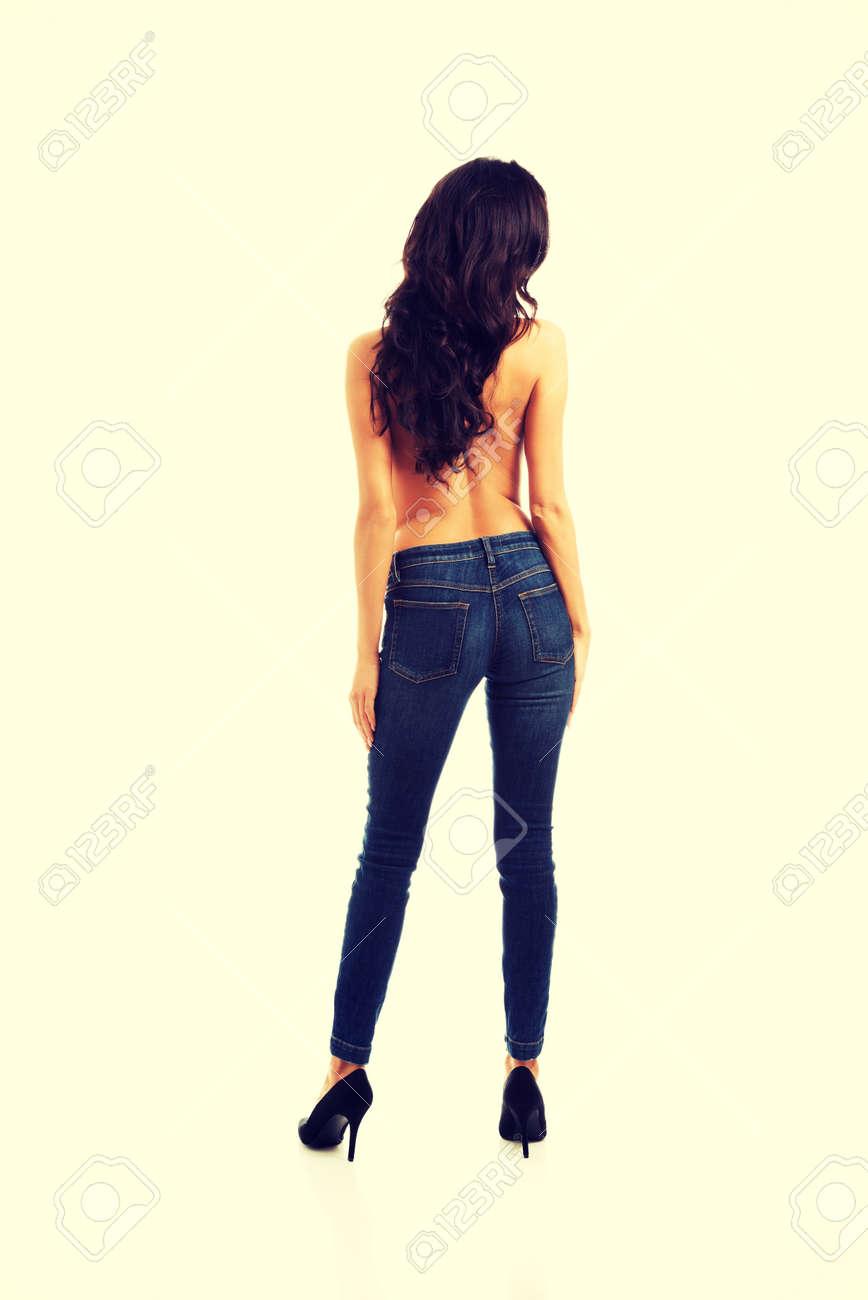 f5fd63f3ef0 Foto de archivo - Sexy topless mujer en pantalones vaqueros y tacones altos  de nuevo a la cámara