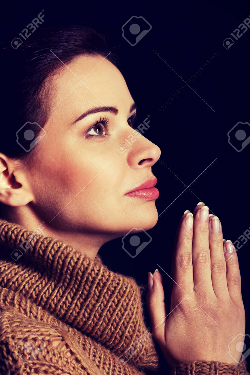 young woman praying over black background stock photo picture and