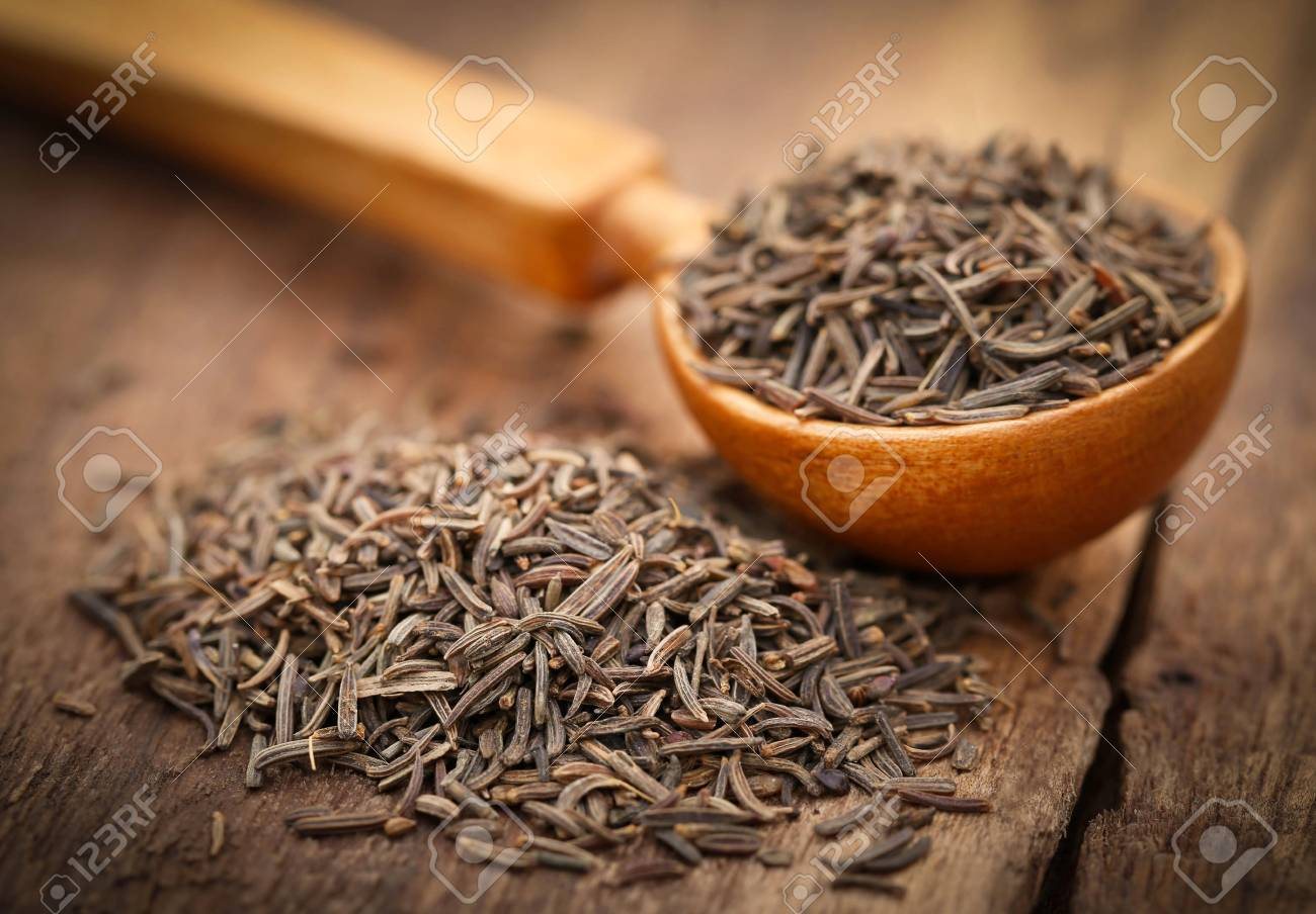Caraway seeds in a spoon on wooden surface - 56283212