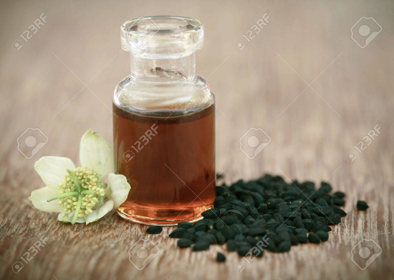 Nigella flower with seeds and essential oil in a glass bottle - 74053769