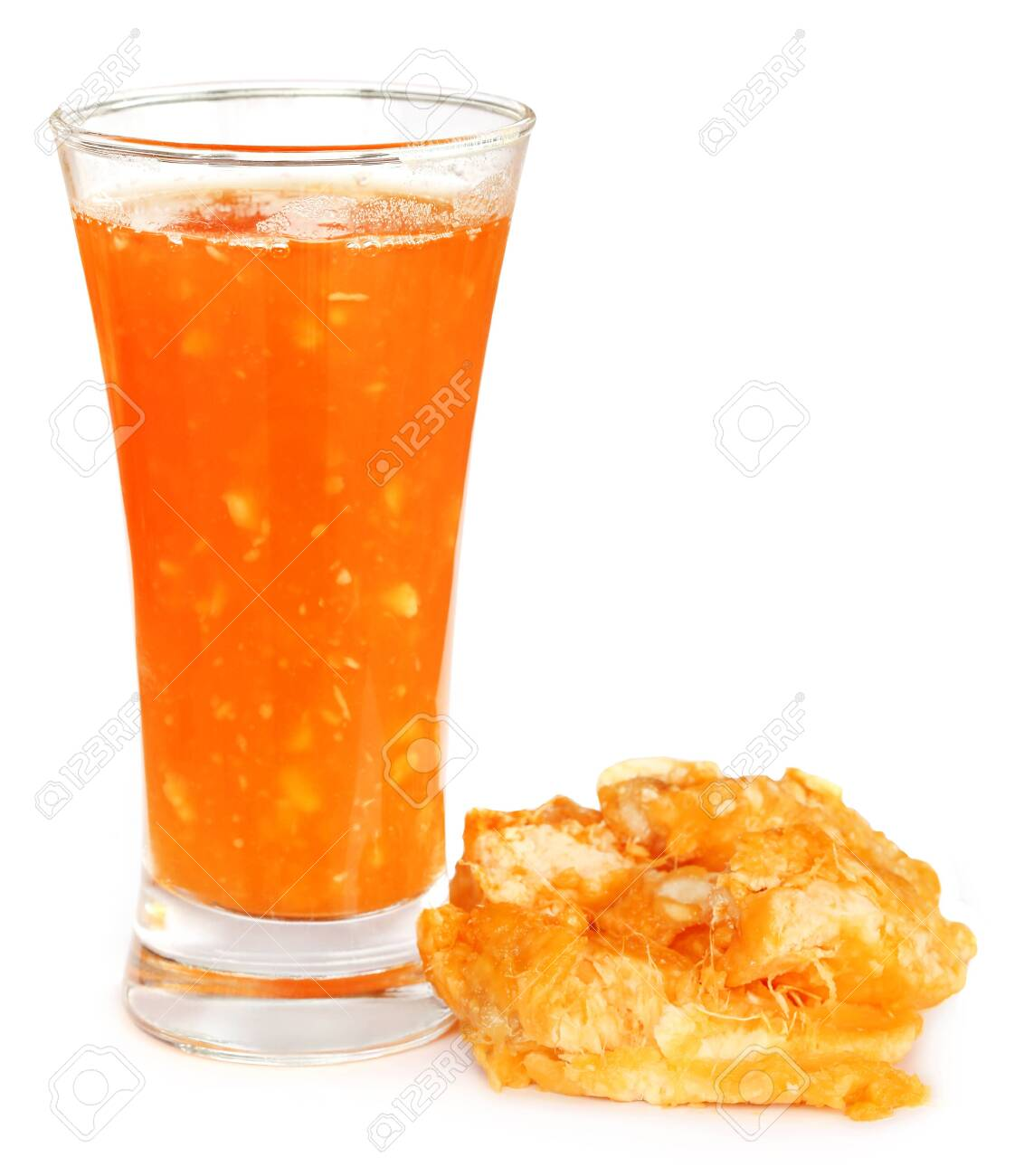 Medicinal Bael fruit with juice in a glass over white background - 124056475