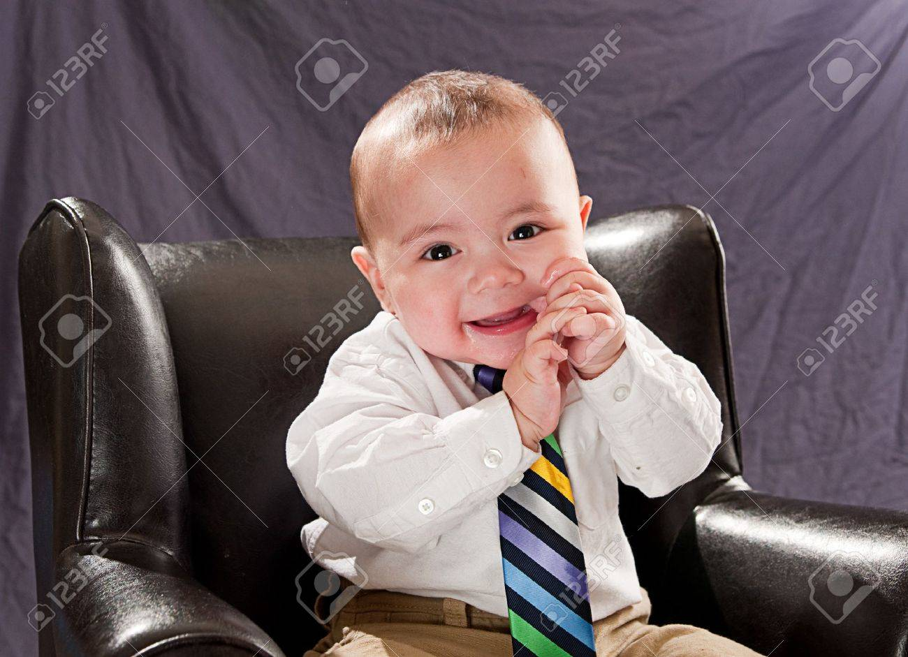 Baby wearing a colorful neck tie smiling and laughing sitting in a leather chair Stock Photo - 7479520