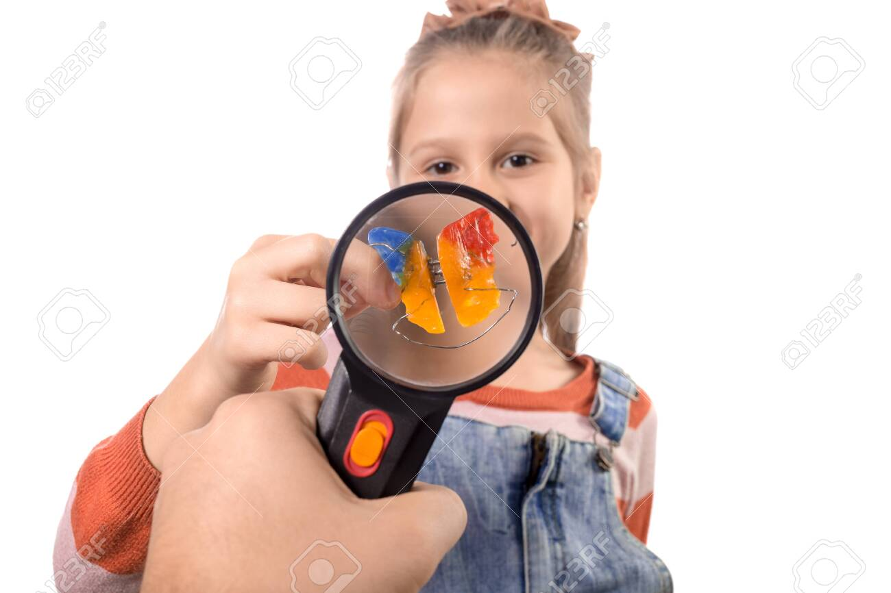 Portrait of a little cute girl with an orthodontic appliance on a white background through a magnifier. - 144507205