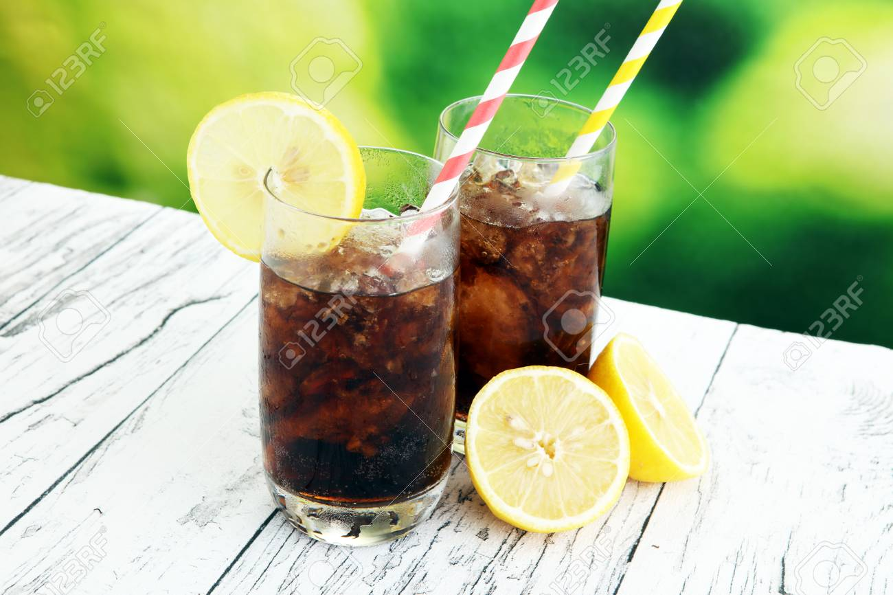 Softdrink with ice cubes, lemon and straw in glass. - 87614486