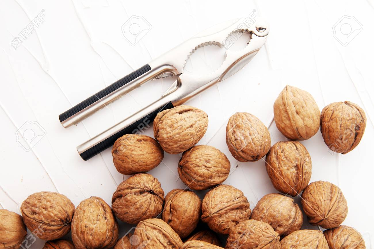 Walnut kernels and whole walnuts on table with a nutcracker - 91586839