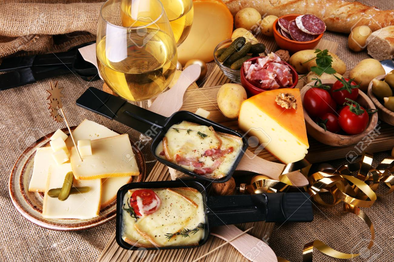 Delicious traditional Swiss melted raclette cheese on diced boiled or baked potato served in individual skillets. - 92315453