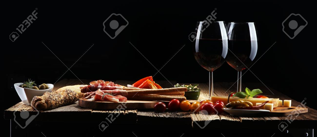 Italian antipasti wine snacks set. Cheese variety, Mediterranean olives, crudo, Prosciutto di Parma, salami and wine in glasses over wooden grunge background - 105452983