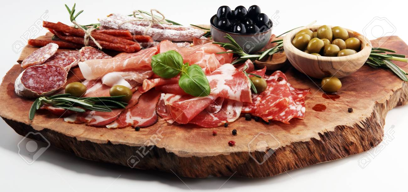 Marble cutting board with prosciutto, bacon, salami and sausages on wooden background. Meat platter appetizers and olives - 114838364