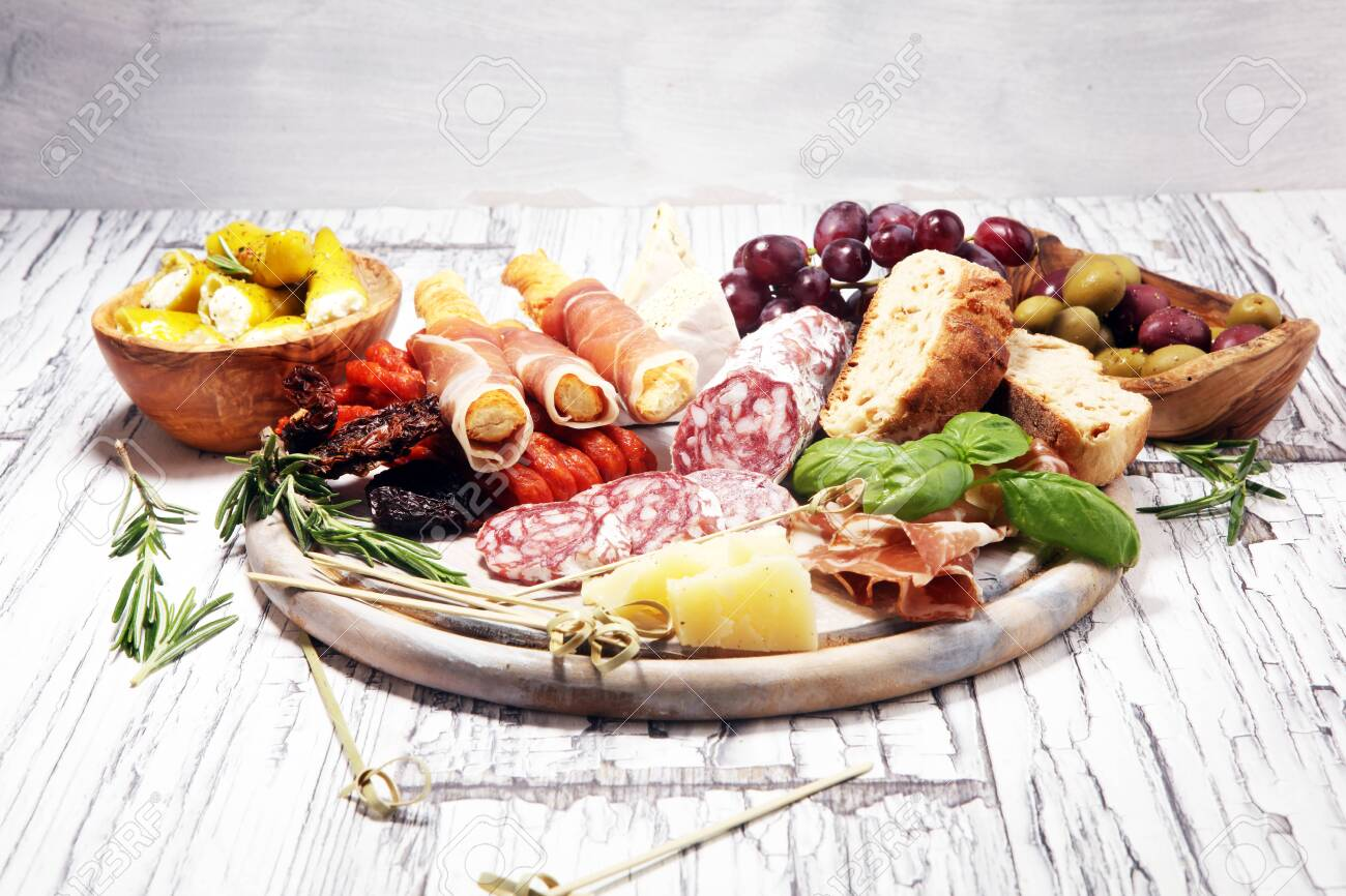 antipasto various appetizer. Cutting board with prosciutto, salami, coppa, cheese,bread sticks and olives on white wooden - 122311965