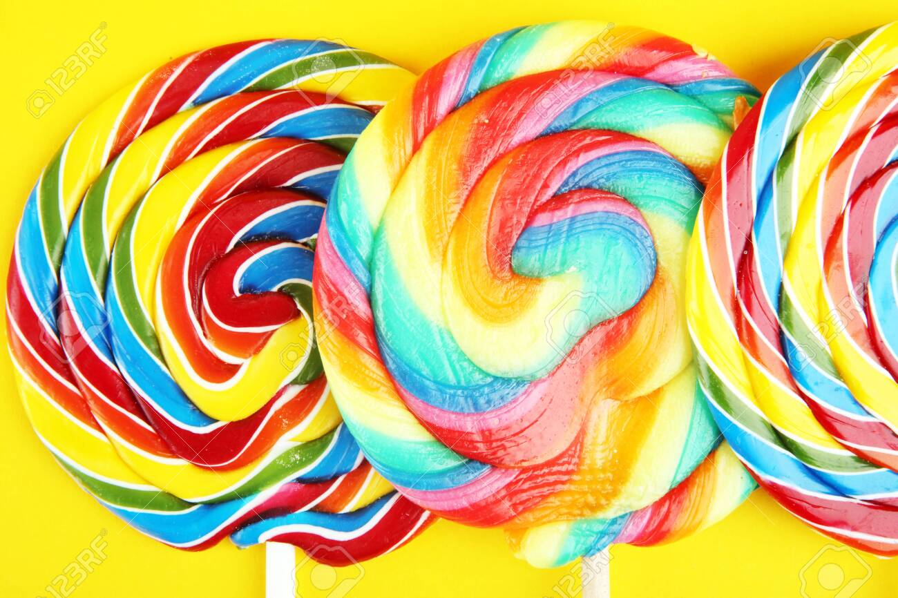 lolly candies with sugar. colorful array of childs lollipops sweets and treats on yellow - 122855774