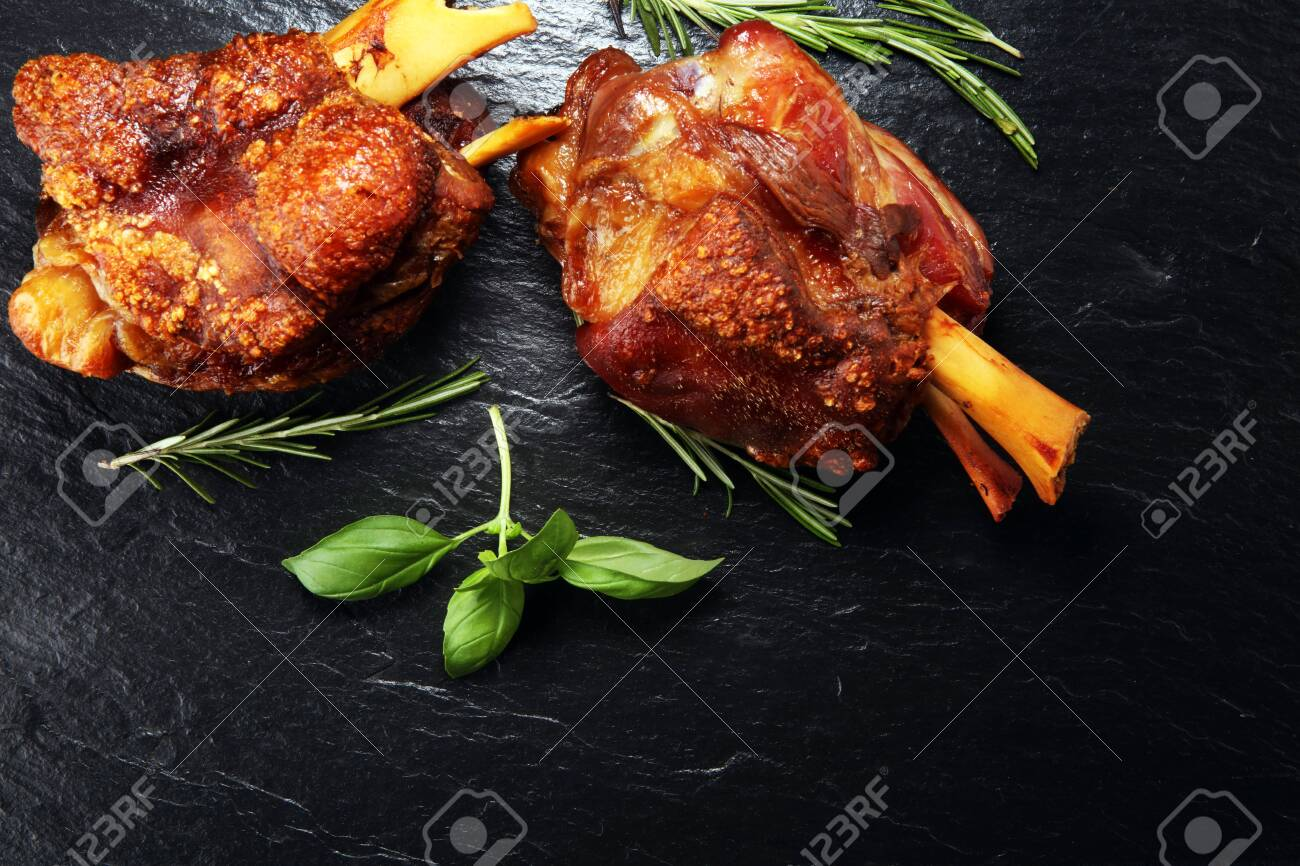 Smoked ham hock with herbs and spices. Roasted pork knuckle. Ham and bacon are popular foods in the west. German Schweinshaxe or Haxe - 124327095