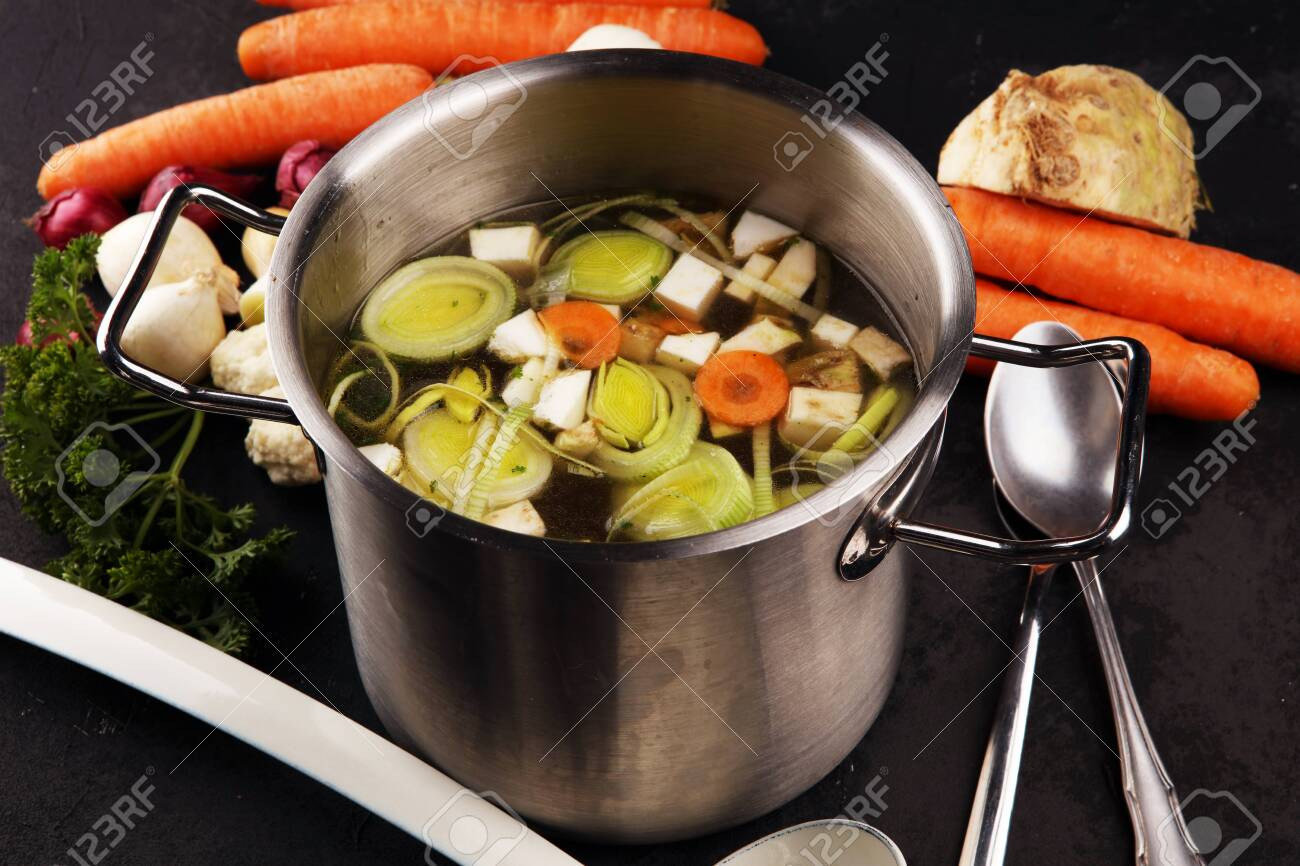 Broth with carrots, onions various fresh vegetables in a pot - colorful fresh clear spring soup. Rural kitchen scenery vegetarian bouillon or stock - 131453967
