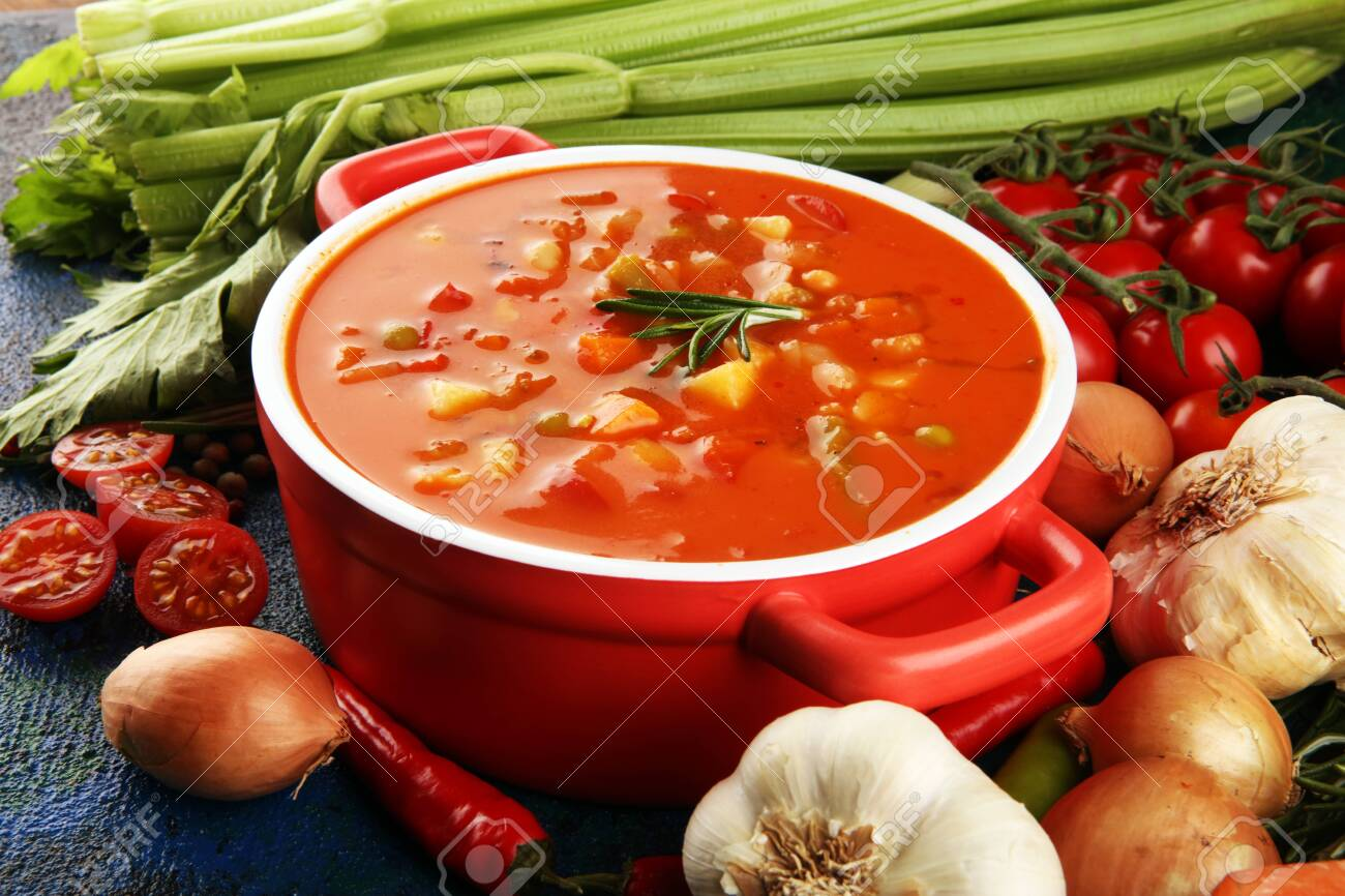 Minestrone soup with tomato in a pan on a light table, top view. Italian soup with pasta and seasonal vegetables. Delicious vegetarian food concept. - 134961281
