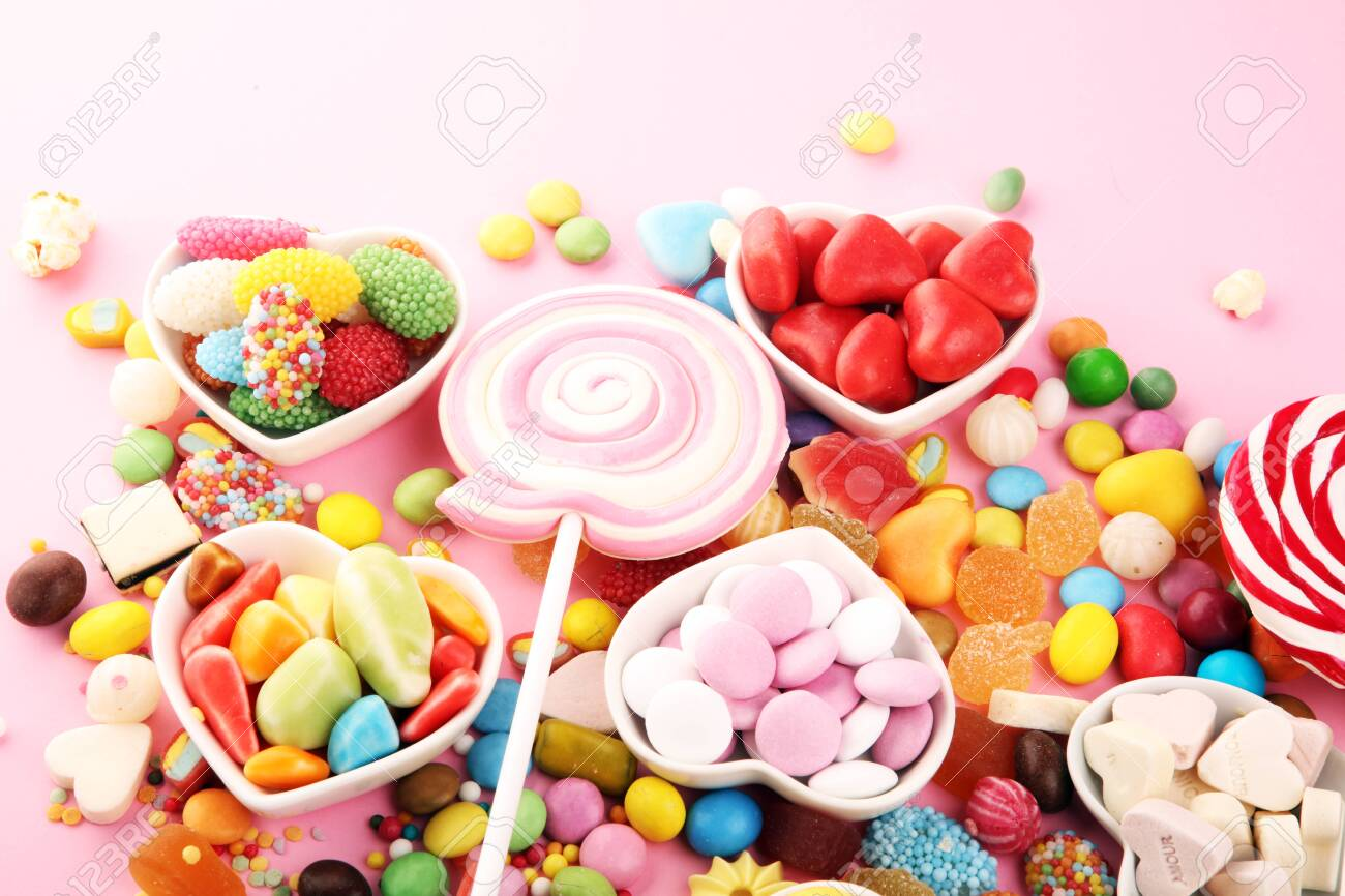 candies with jelly and sugar. colorful array of different childs sweets and treats on pink - 136861147
