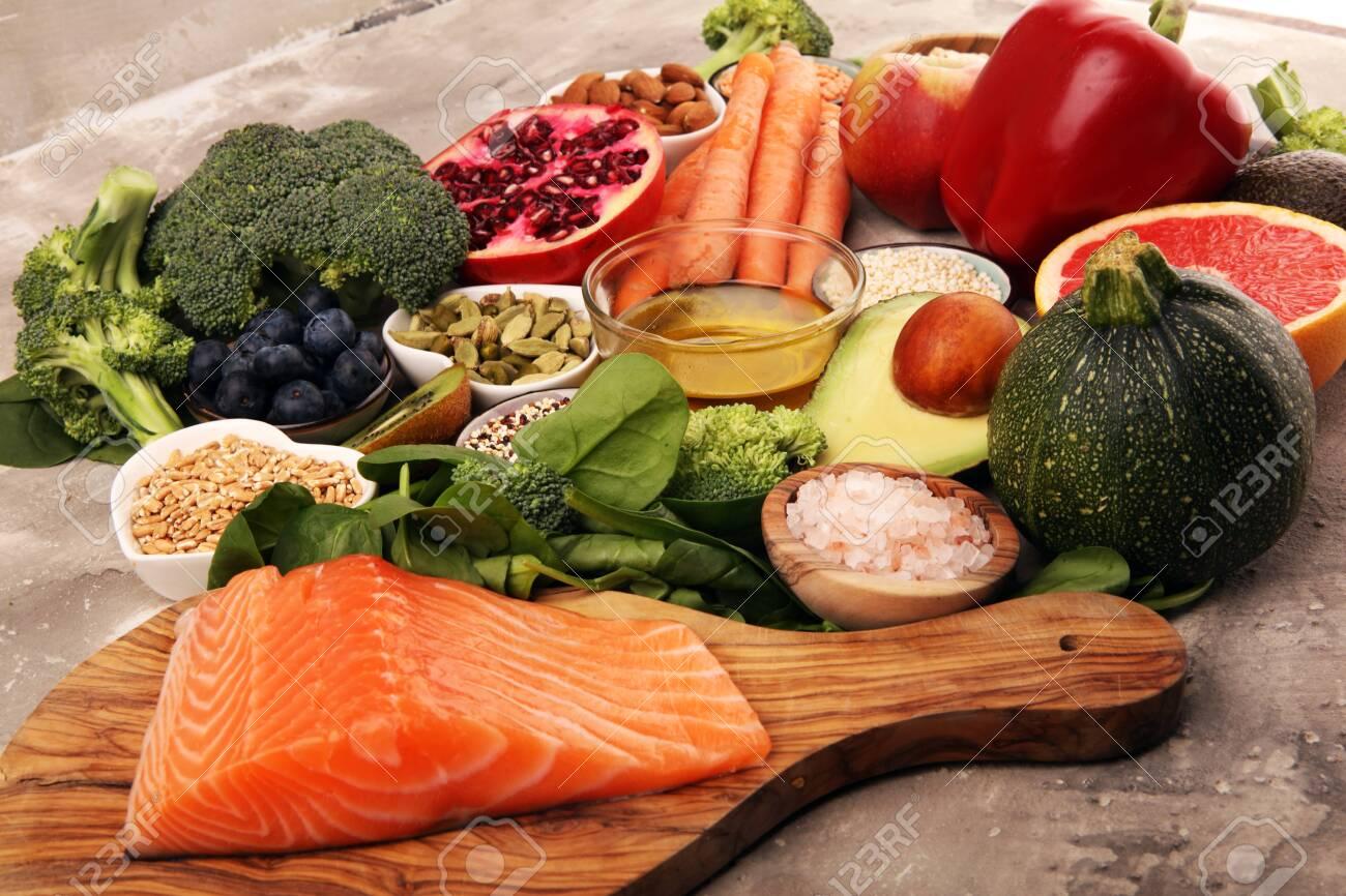 Healthy food clean eating selection: fish, fruit, vegetable, cereal, leaf vegetable on background - 141252240