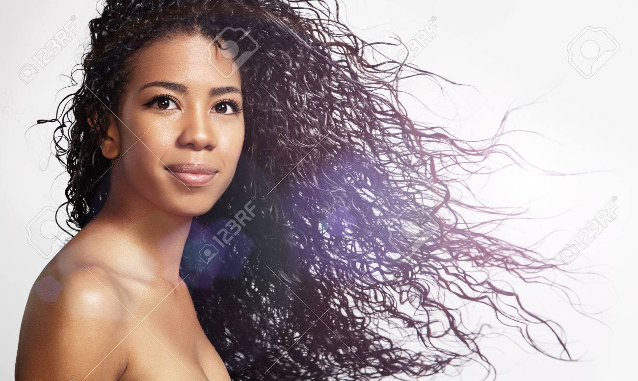 happy black woman with blowing curly hair - 34674586