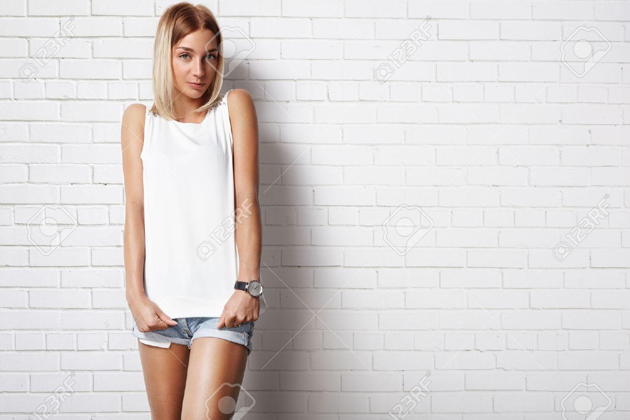 woman wearing white t-shirt against brick wall - 34674786
