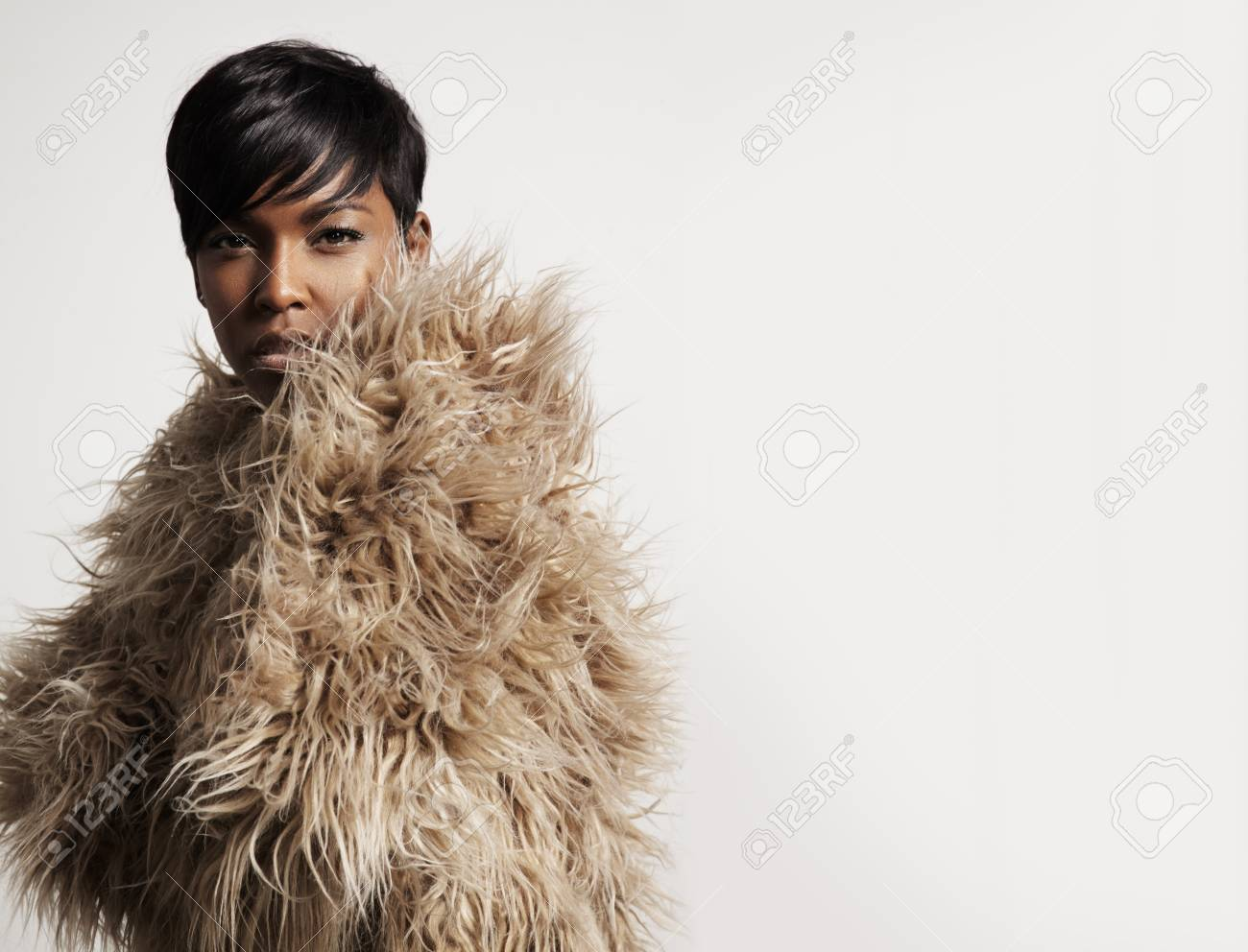 woman wearing a faux fur and watching at camera - 35825212