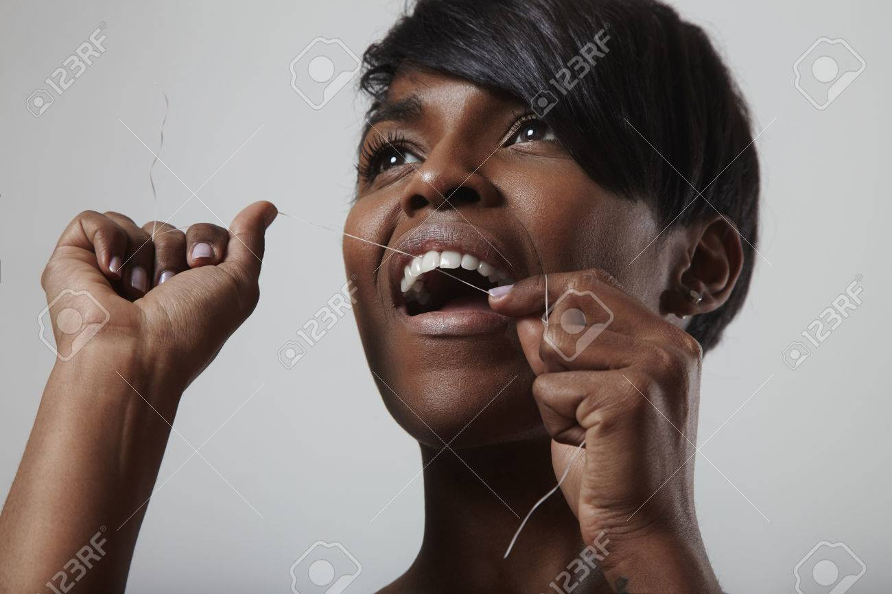 Young woman smiling girl cleaning her white teeth with dental floss - 38272968