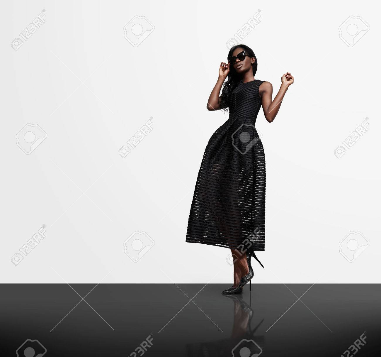 woman wearing black dress on a white wall background and black cristal flor - 42417396