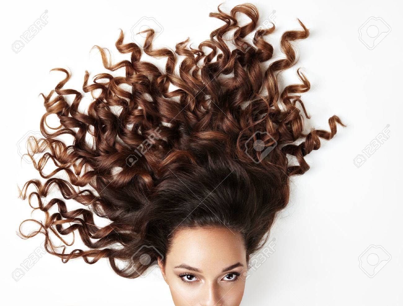 curly hair and part of woman's face, looking at the camera - 45147450