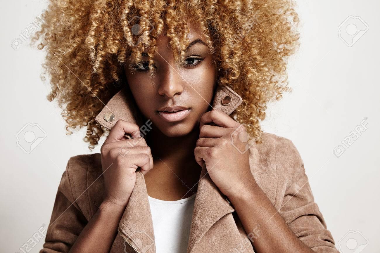 mujer de negro viste chaqueta de color beige pelo rizado foto de archivo