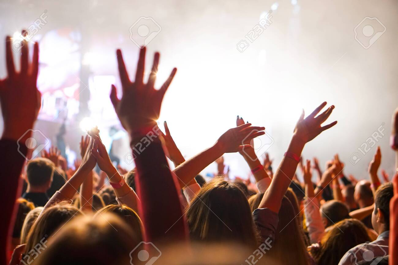 Crowd at a music concert, audience raising hands up - 138765424
